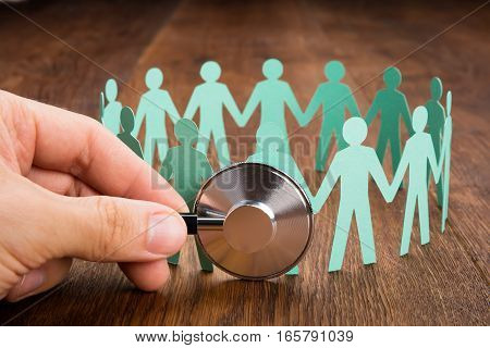 Person Using Stethoscope On Papercut Representing People Holding Hands Together On Wooden Desk