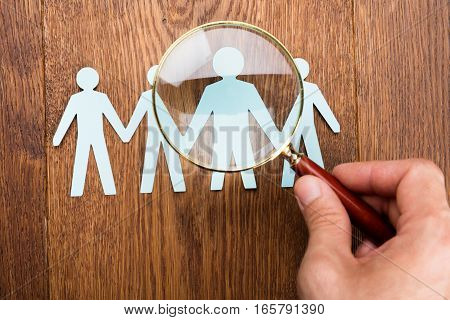 High Angle View Of Person Using Magnifying Glass On Papercut At Wooden Desk