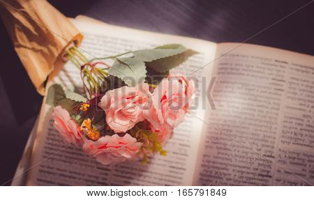 Artificial roses place on unfocused book- select focus and pink color effect