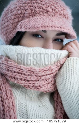 Portrait of girl in sweater hat and scarf. She wrapped herself in sweater and scarf.