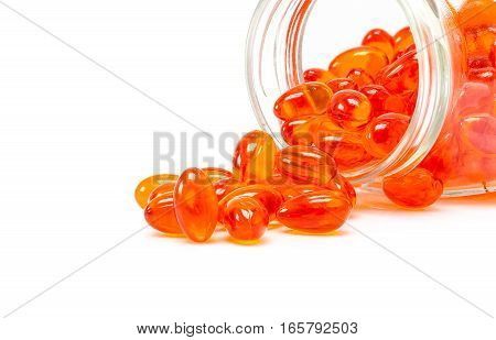 Red supplement capsules for health spill out from glass bottle isolated on white background