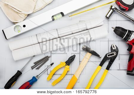 High Angle View Of Tools And Equipment Are Placed On Blueprint In Office