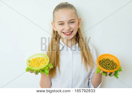 Happy fitness girl holding two bowls with canned peas and corn and looking at camera isolated on a white background