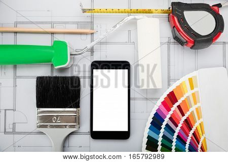 Mobile Phone Showing Blank Screen On Blueprint And Other Materials On Office Desk