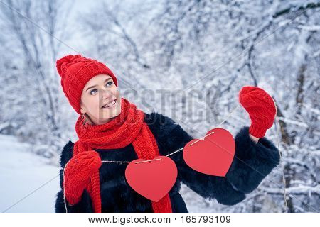 Love and valentines day concept. Smiling woman holding garland of two red paper hearts shape - blank copy space for letters or text, looking up over winter landscape