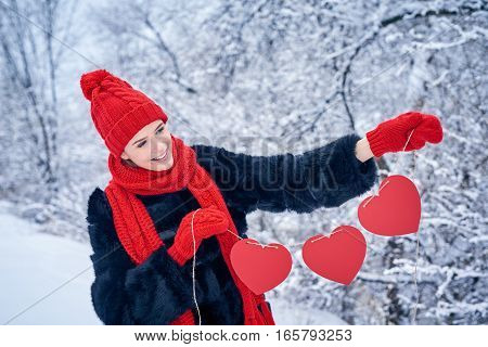 Love and valentines day concept. Smiling woman holding garland of three red paper hearts shape - blank copy space for letters or text, looking down to the side over winter landscape
