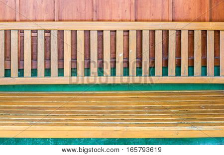 Old teak bench near the green wall of the local restaurant.