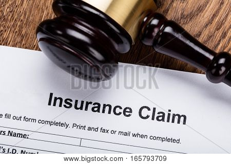 Close-up Of Wooden Gavel On Insurance Claim Form At Wooden Desk