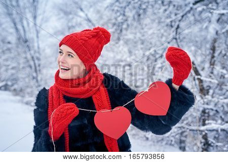 Love and valentines day concept. Happy laughing woman holding garland of two red paper hearts shape - blank copy space for letters or text, looking away over winter landscape