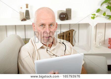 mature man using tablet computer sitting on sofa