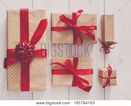 Top view of Gift boxes on white wood background. Presents in craft paper decorated with red ribbon bows. Birthday, valentine and other holidays concept.