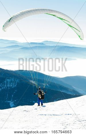 Paraglider preparing to get launched into air at the peak of a mountain