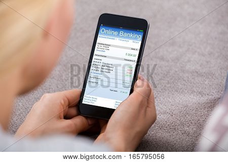 Close-up Of Young Woman Online Banking On Mobile Phone