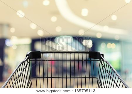 Shopping cart in shopping blue mall bakground
