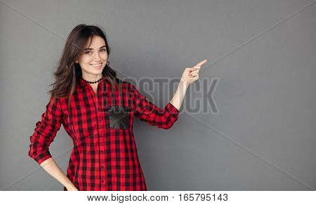 Young brunette woman showing with her finger to copy space isolated gray background