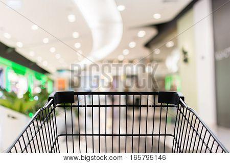 Shopping cart in shopping blur mall bakground
