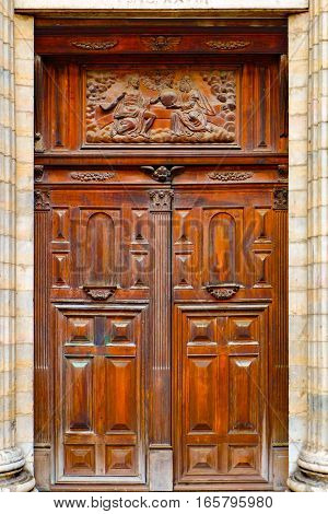 Antique wooden double door of an old church. Above the main entrance a religious relief is carved into the wood, the entry itself is ornate with geometric shapes and other decorative ornaments. The door is rectangle and surrounded by stone columns.