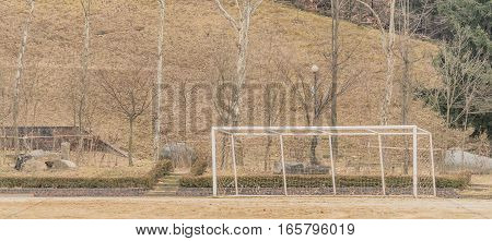 Soccer goal at the edge of a dirt field with trees in the background