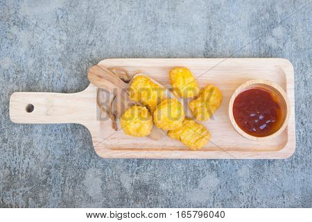 Chicken Nuggets on wooden cutting board with ketchup