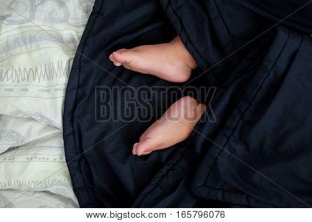 Bare feet of a cute newborn baby in warm blue blanket.