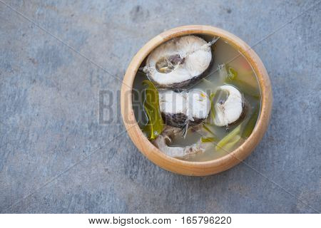 Tom yum soup with fish in bowl wooden