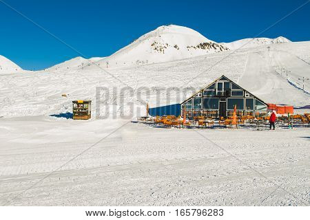Photo of the Beautiful winter landscape on skiing resort with ski lodge. White snow cover. Tourism industry. Negative space for text. Extreme sport. Active holiday. Free time concept.
