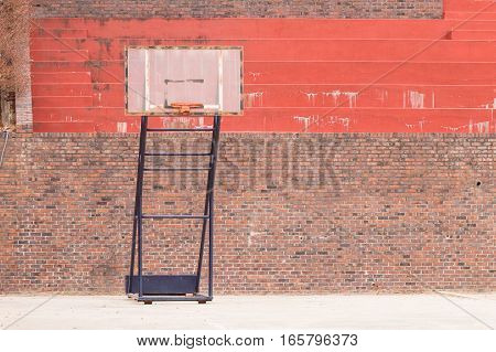 Movable basketball goal in front of bleachers made of red brick and concrete