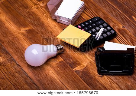 set of stationery for office: lightbulb box phone blanks hole puncher calculator pin stickers on brown vintage wooden background side view