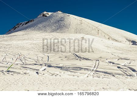 Photo of the Gudauri - paradise for freeride. Winter mountains background with ski slopes and ski lifts. Skiing resort. Extreme sport. Active holiday. Tourism industry, travel concept.