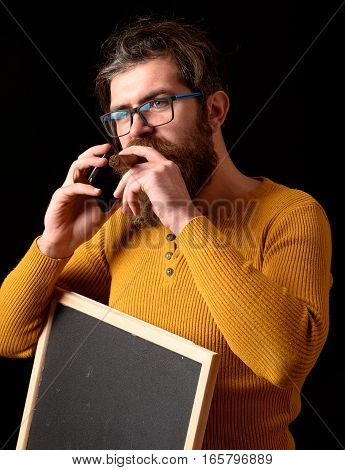 handsome bearded hipster man with long lush beard moustache and stylish hair on serious face in glasses yellow sweater holding board with cigar speaks by phone on black studio background copy space