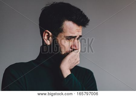 Young man with a problem crying, studio shot