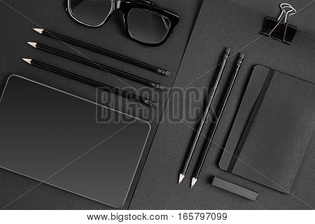 Blank notepad with clips, pens and glasses flat lay. Top view on set of black office supplies and spectacles, free space. Art, business, creation, imagination, education, stationery concept