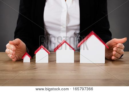 Businesswoman Protecting Different Size Houses In Row On Wooden Table. Property Growth Concept