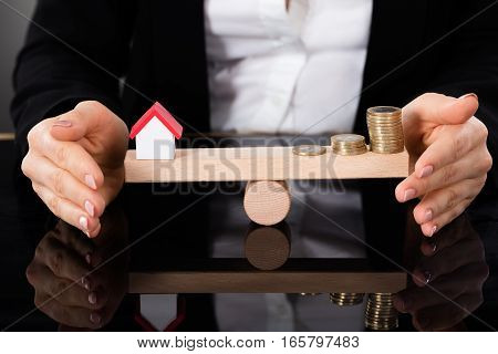 Businesswoman Hand Covering Balance Between Model House And Money Coins On A Seesaw