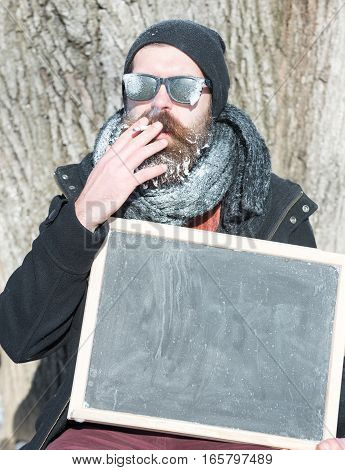 Handsome man hipster with beard and moustache in black sunglasses covered with white frost smokes cigarette holding blank black board or chalkboard on winter day on natural background copy space