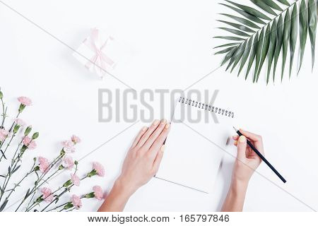 Woman's Hand Writing In A Notebook At The Desk, Top View