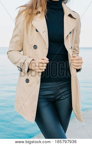 Slender Girl In A Beige Coat And Black Pants On The Beach