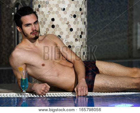 Handsome man muscular bearded hipster or sexy macho with muscle torso body with cocktail in glass lies near pool indoors on blue water background