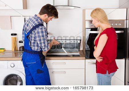 Young Woman Looking At Male Repairman Examining Stove In Kitchen