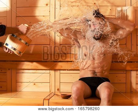 Excited man or bather with muscular sexy torso body wet with big splash of water from bucket in sauna thermal bath on wooden background