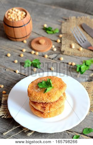 Pea patties on a white plate. Spicy vegan patties cooked from yellow dried peas and decorated with fresh parsley. Decorative barrel, fresh parsley on old wooden background. Vegan dish concept. Closeup