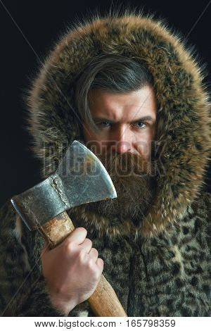 handsome bearded man or woodman guy with fashionable mustache and beard on serious face in brown fur coat holds sharp axe or ax on black background