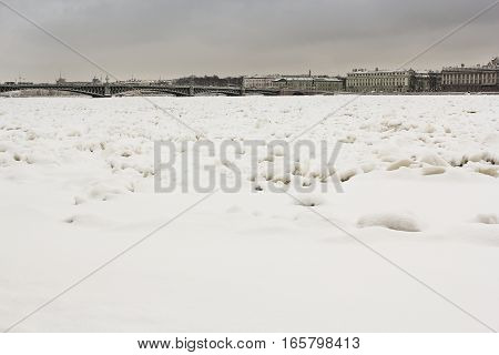 Ice hummocks on the Neva. Types of quays of St. Petersburg with winter Neva River.