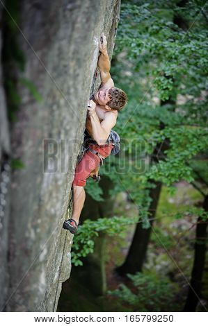 Muscular Rock Climber Climbs On Overhanging Cliff
