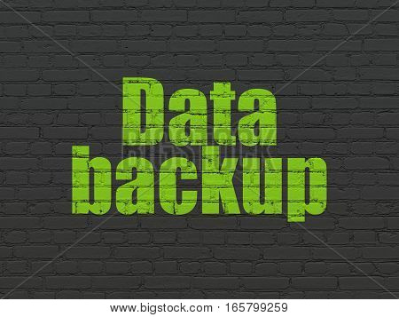 Data concept: Painted green text Data Backup on Black Brick wall background