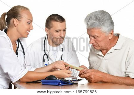 man and woman doctors with patient, discuss health problems
