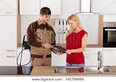 Young Smiling Woman Signing Invoice From Exterminator Worker After Pest Control Work In House Kitchen