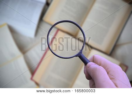 Hand holding a magnifying glass while searching information.