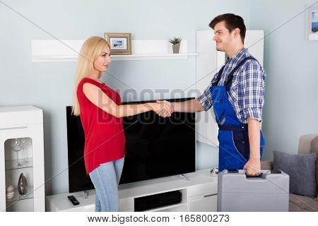 Young Male Technician Shaking Hand With Smiling Young Woman At Home