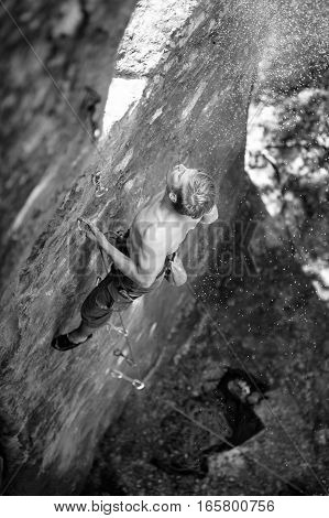 Young man rock-climbing on large boulder blowing magnesium from fastening . Outdoor summer day. Black and white